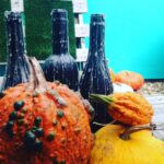 pumpkins and bottles with wax candle drips